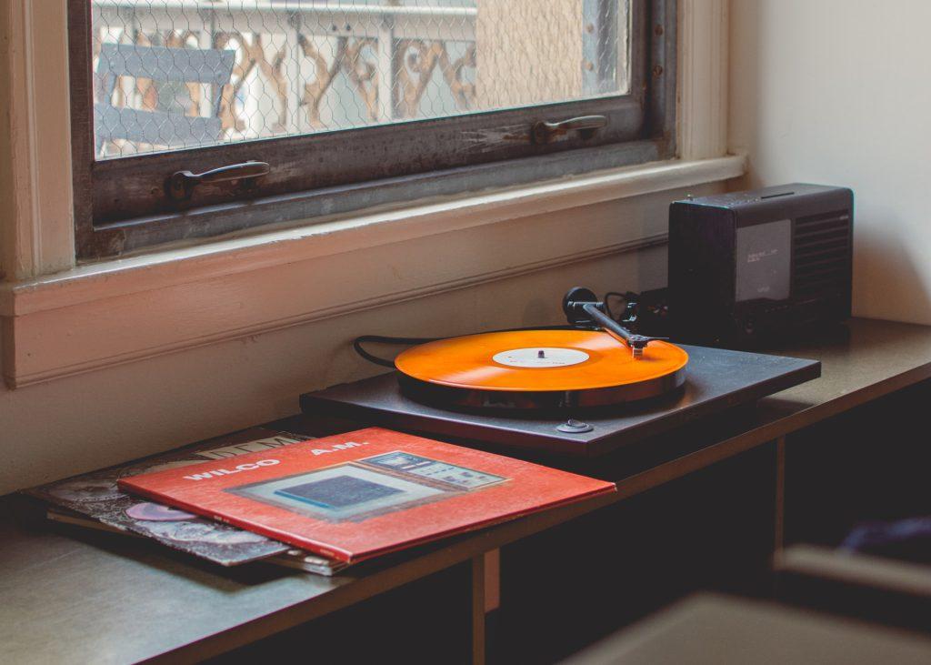 Vitrola tocando um disco de vinil laranja, item interessante para se usar em uma decoração vintage