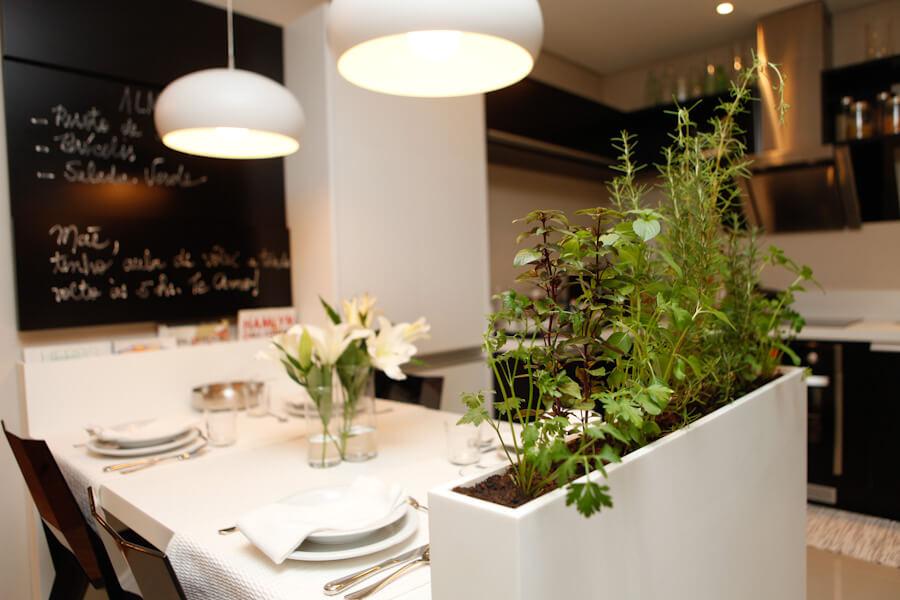 Cozinha com mesa de jantar posta e um pequeno vaso de ervas ao lado.