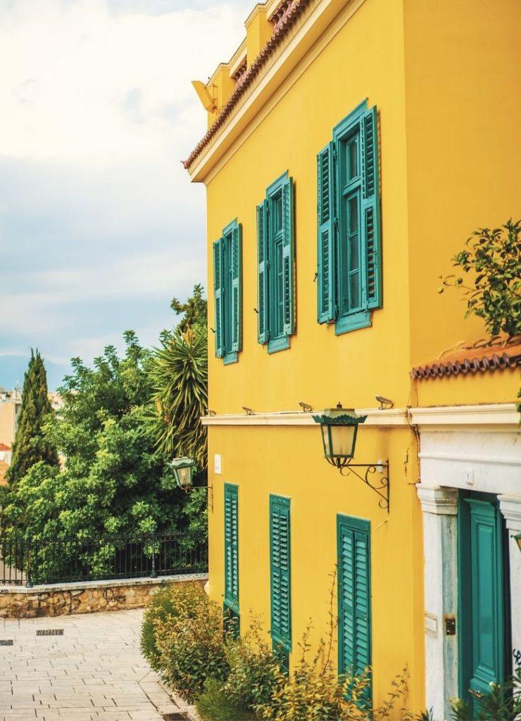 Fachada de casa antiga com paredes amarelas e janelas verdes.