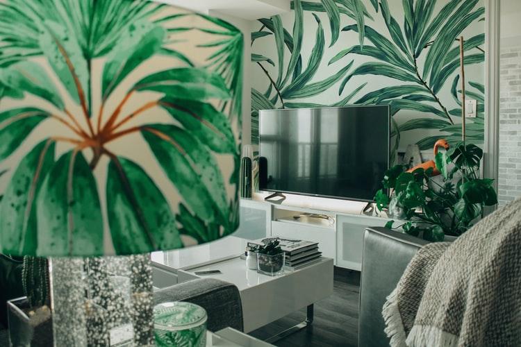 Sala de estar com papel de parede com estampa de plantas e um abajur, também estampado com a imagem de plantas.