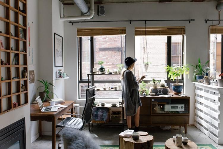 Pessoa em sua sala de estar, parada em frente a janela, com algumas plantas.