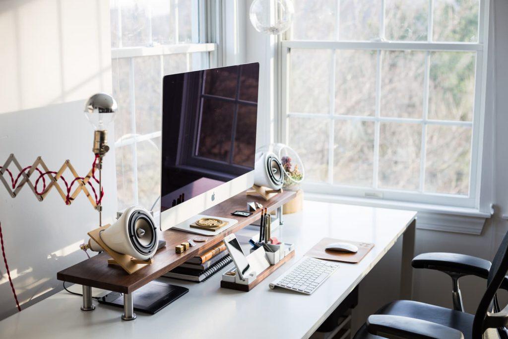 Escritório em casa contando com uma escrivaninha branca, um computador da Apple e caixas de som,.
