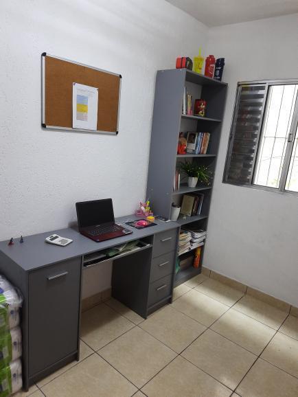 Escritório em casa de uma cliente Madesa contando com um conjunto de escrivaninha e estante livreiro.