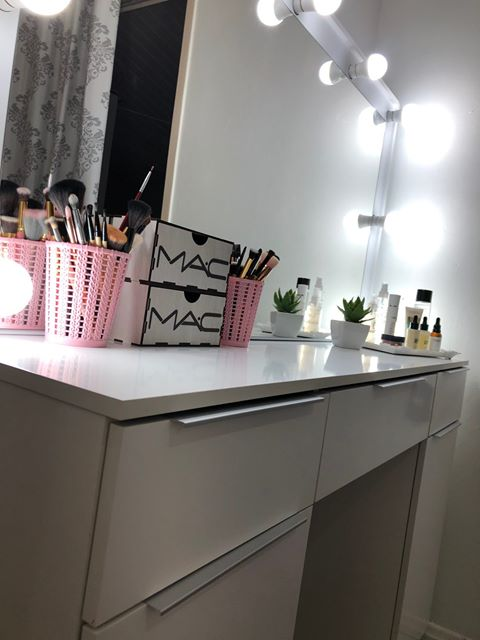 Penteadeira Madesa branca com espelho. A imagem foca no tampo da penteadeira, que possui alguns itens de maquiagem organizados.