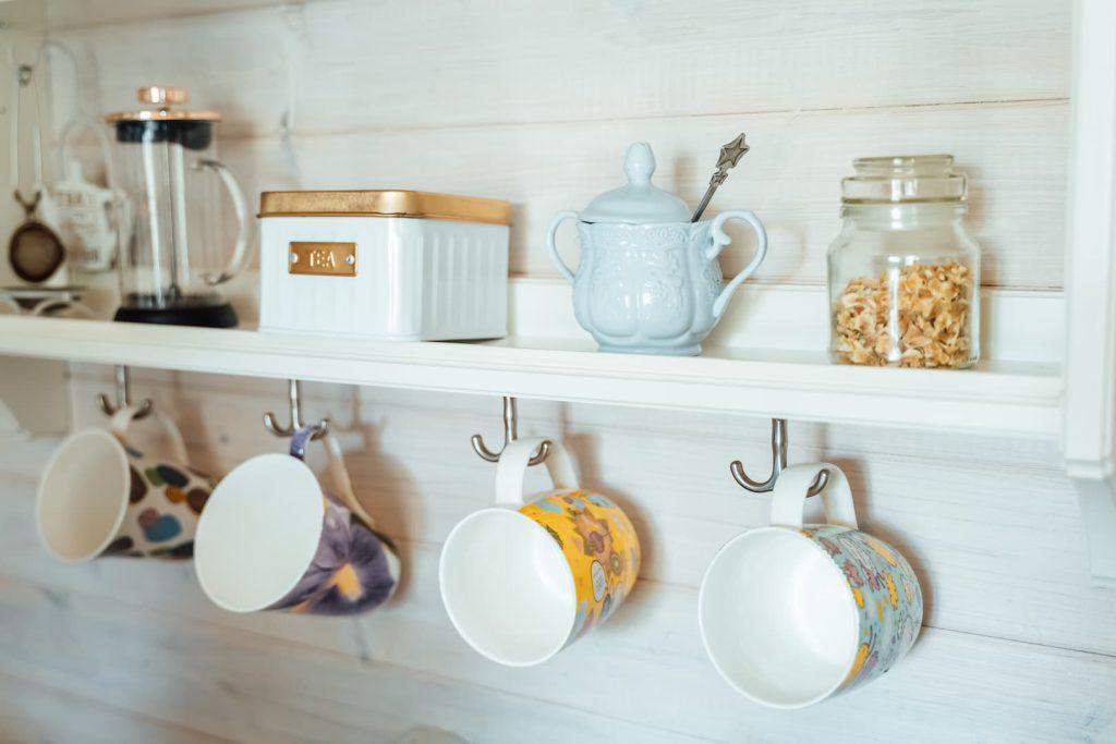 Prateleira na cozinha com ganchos para pendurar xícaras.