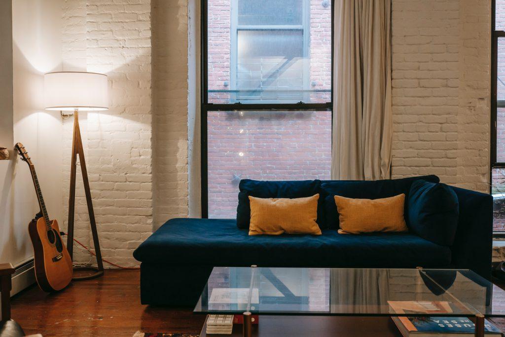 Sala de um apartamento pequeno decorada com um sofá azul, amolfadas amarelas, violão, luminária e parede de tijolinhos pintada de branco.
