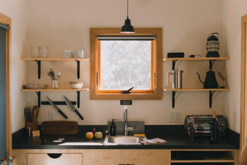 Cozinha pequena com prateleiras na parede para otimização de espaço.