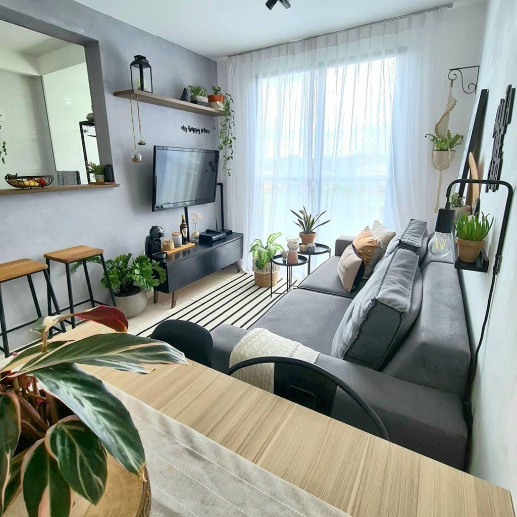Sala de apartamento pequeno decorada com sofá, rack Madesa Reims e plantas.