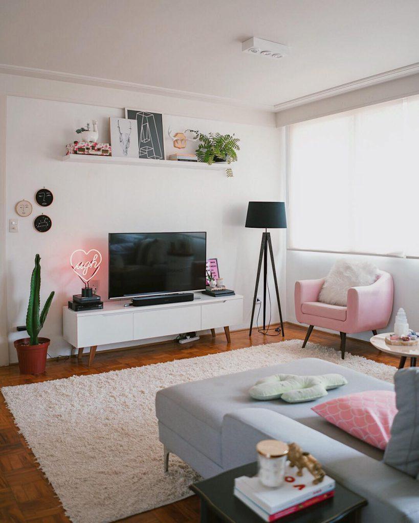 Sala de apartamento com paredes brancas e objetos cor de rosa como exemplo de como decorar um apartamento pequeno.