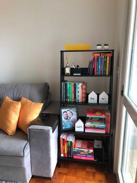 Estante escada Madesa com livros ao lado de um sofá