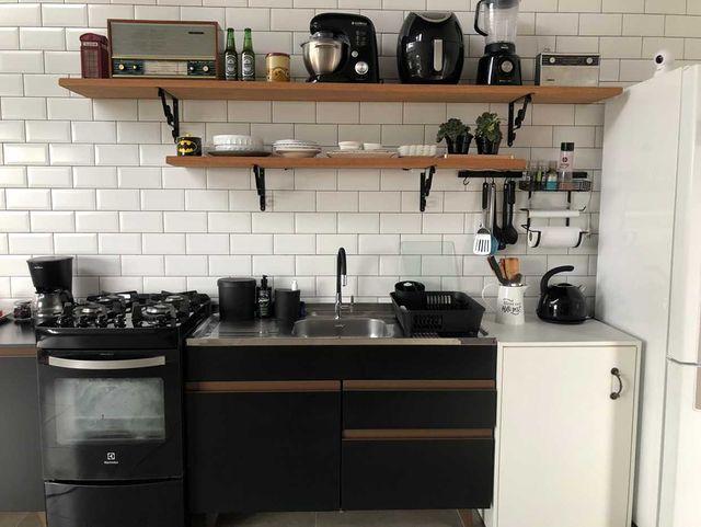 Cozinha pequena com gabinete preto Madesa e prateleiras na parede.