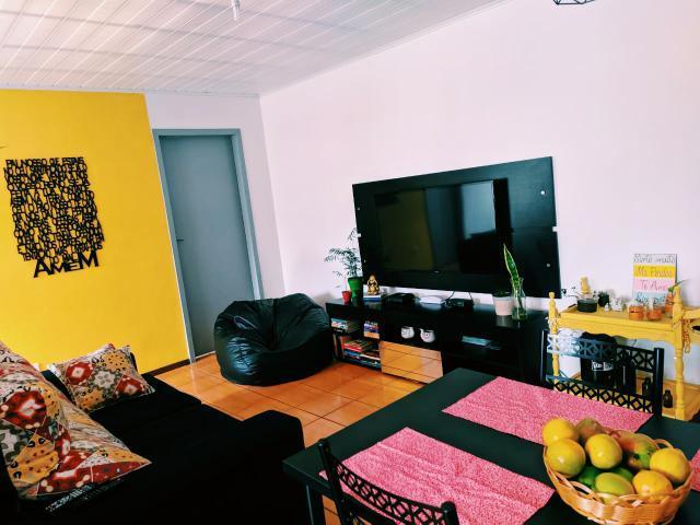 Sala de cliente Madesa com paredes rosas e amarelas e móveis pretos, um exemplo claro de como combinar cores complementares.