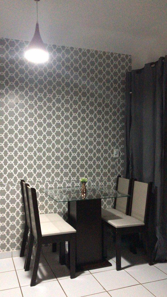 Sala de jantar Madesa, contando com uma mesa e quatro cadeiras, e decorada com papel de parede.