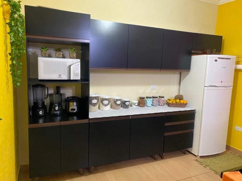 Cozinha preta entre paredes amarelas vibrantes.
