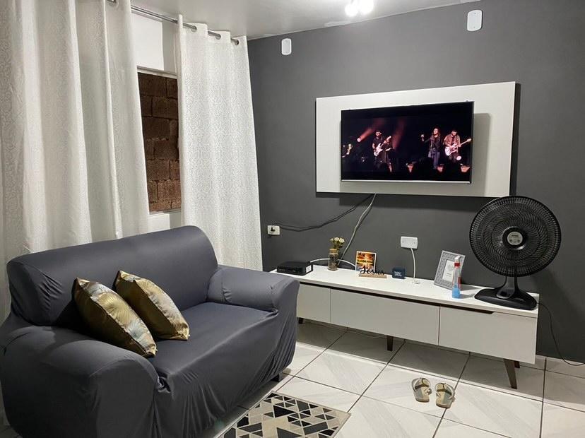 Sala com paredes cinzas e brancas e rack e painel Madesa na cor branca, como exemplo da combinação entre o branco, o cinza e o preto.