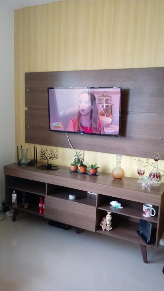 Sala de estar com papel de parede amarelo e rack e painel Madesa.