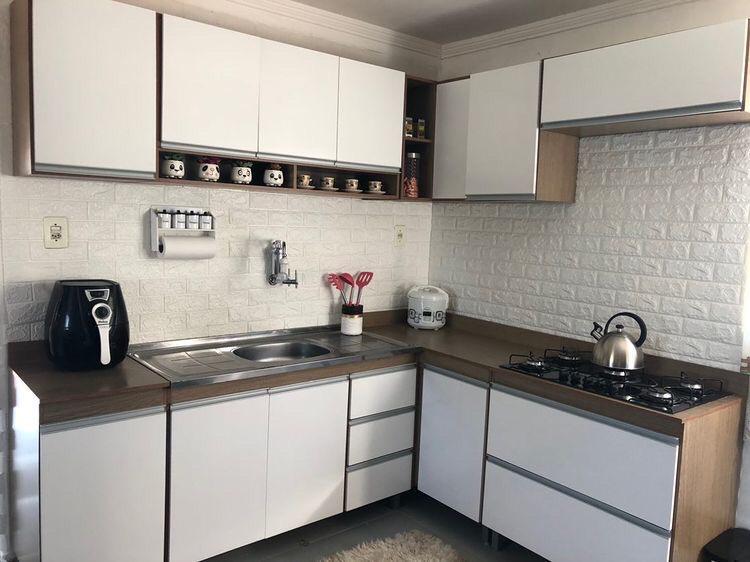 Cozinha Madesa Glamy em frente a um papel de parede 3D de tijolinhos.