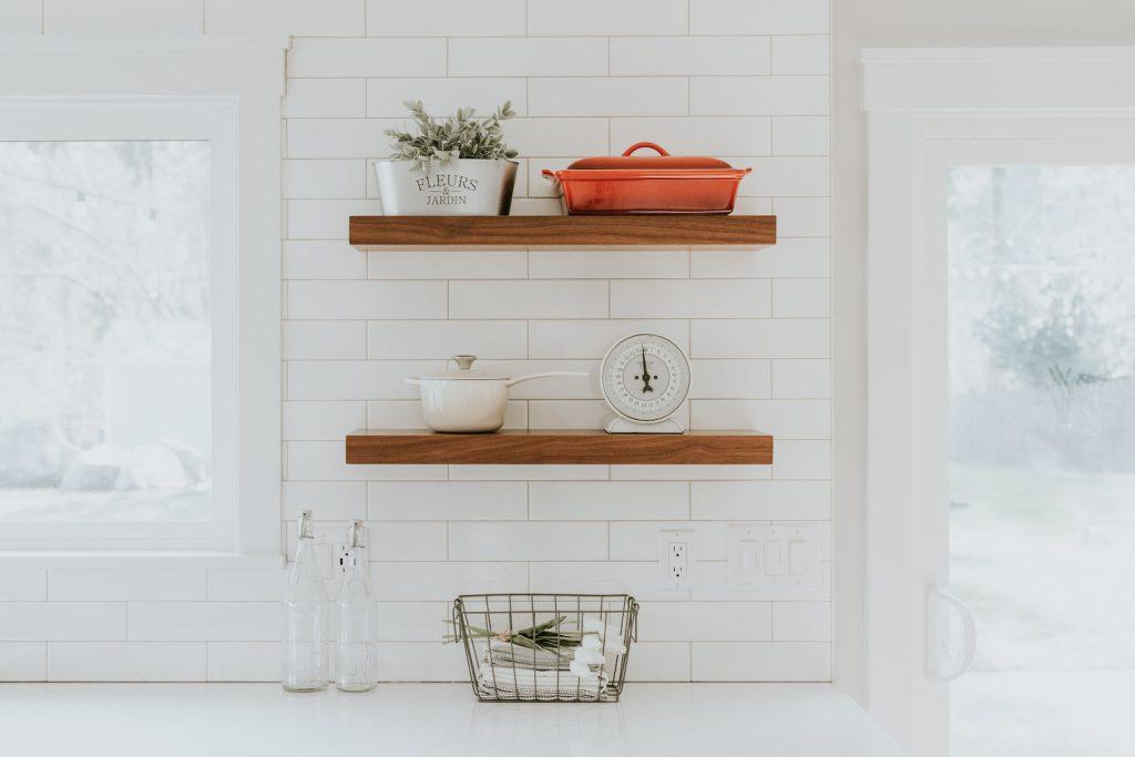 Imagem de uma prateleira de madeira em uma cozinha com parede de tijolinhos branca. Na prateleira há algumas panelas e objetos decorativos.