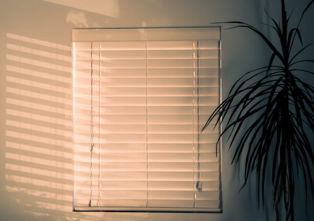 A imagem contém uma persiana branca, um dos tipos de cortina mais modernos e funcionais.