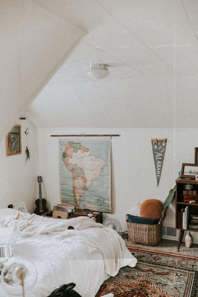Quarto decorado no estilo boho, contando com tapetes e posters na parede.