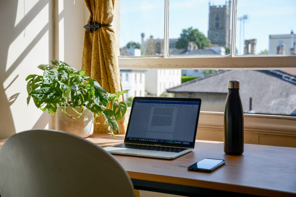 Home office no quarto montado em frente a uma janela, com notebook, celular, garrafa d'água e decorado com uma planta.