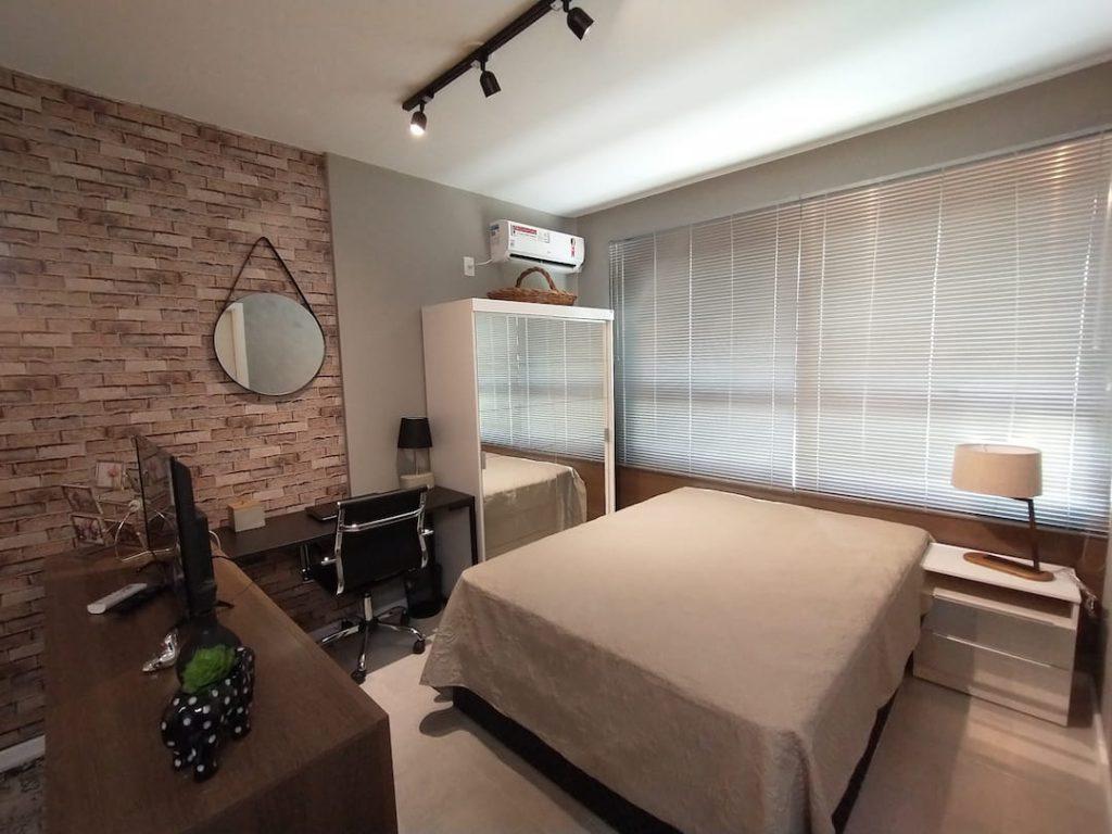 Quarto do apartamento da Fun House contando com uma cama, mesas de cabeceira da Madesa, guarda-roupa espelhado e escrivaninha.
