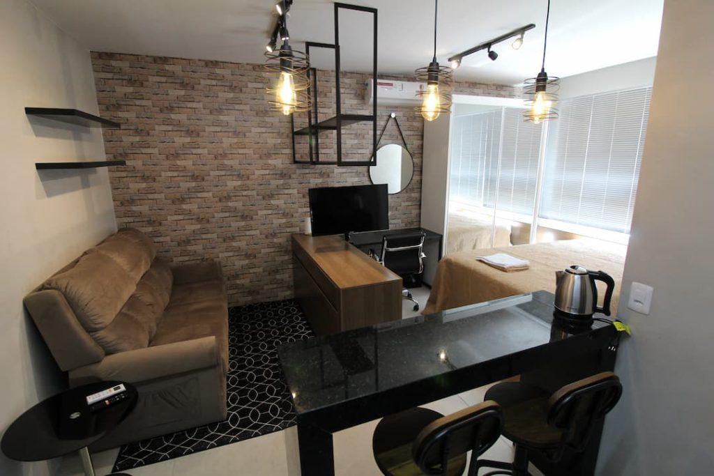 Vista da sala do apartamento, com sofá, TV, luzes pendentes. É possível ver um pedaço da bancada da cozinha na foto.