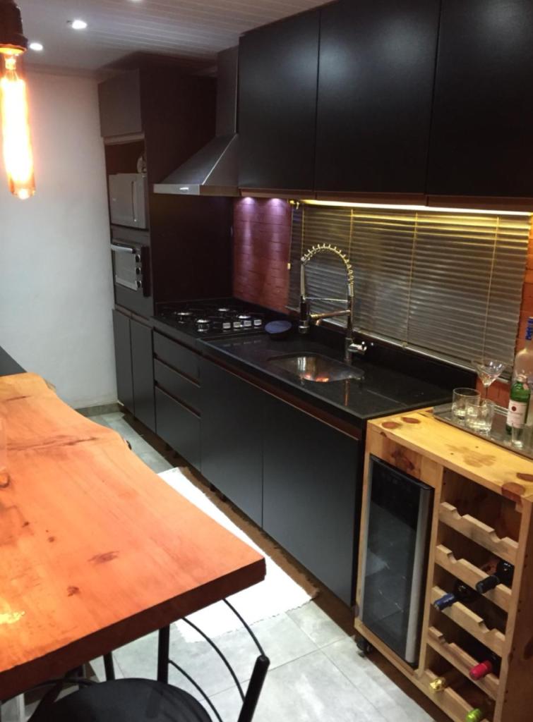 Cozinha industrial de cliente Madesa com móveis pretos e detalhes em madeira.