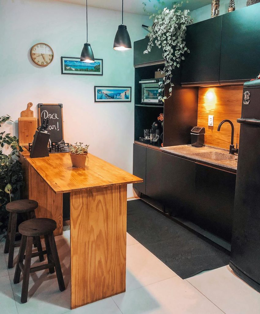 Cozinha com móveis pretos e com detalhes em madeira, que combinam muito com o estilo industrial.