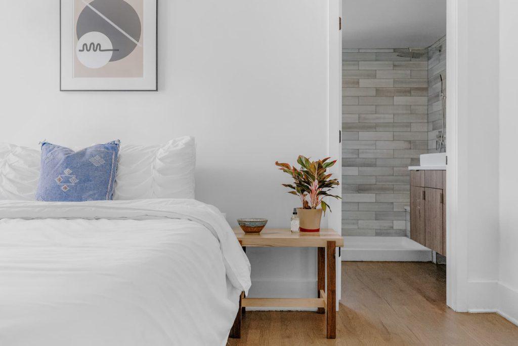 Quarto com paredes brancas, piso de madeira e alguns detalhes minimalistas como o uso de quadros geométricos.