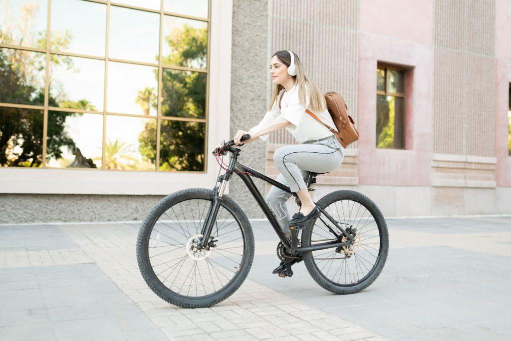 Mulher andando de bicicleta pela cidade, um exemplo de prática de uma vida sustentável.