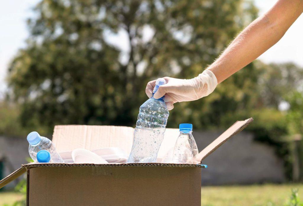 Mão com luva de plástico jogando uma garrafa plástica em uma caixa de papelão como exemplo de como praticar a sustentabilidade em casa.