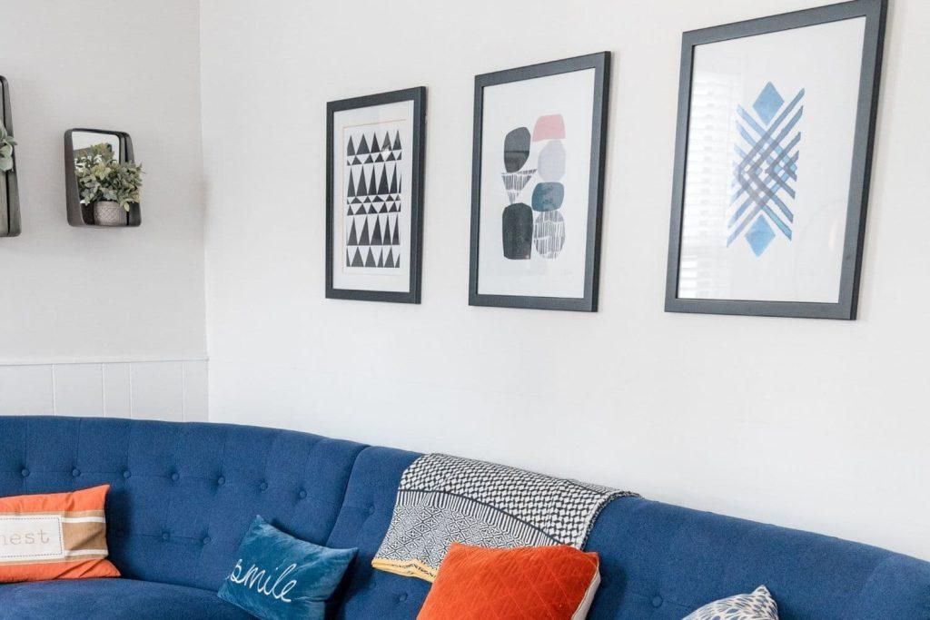 Sala de estar com sofá azul, almofadas coloridas e quadros pendurados na parede como exemplo de como decorar apartamento alugado.