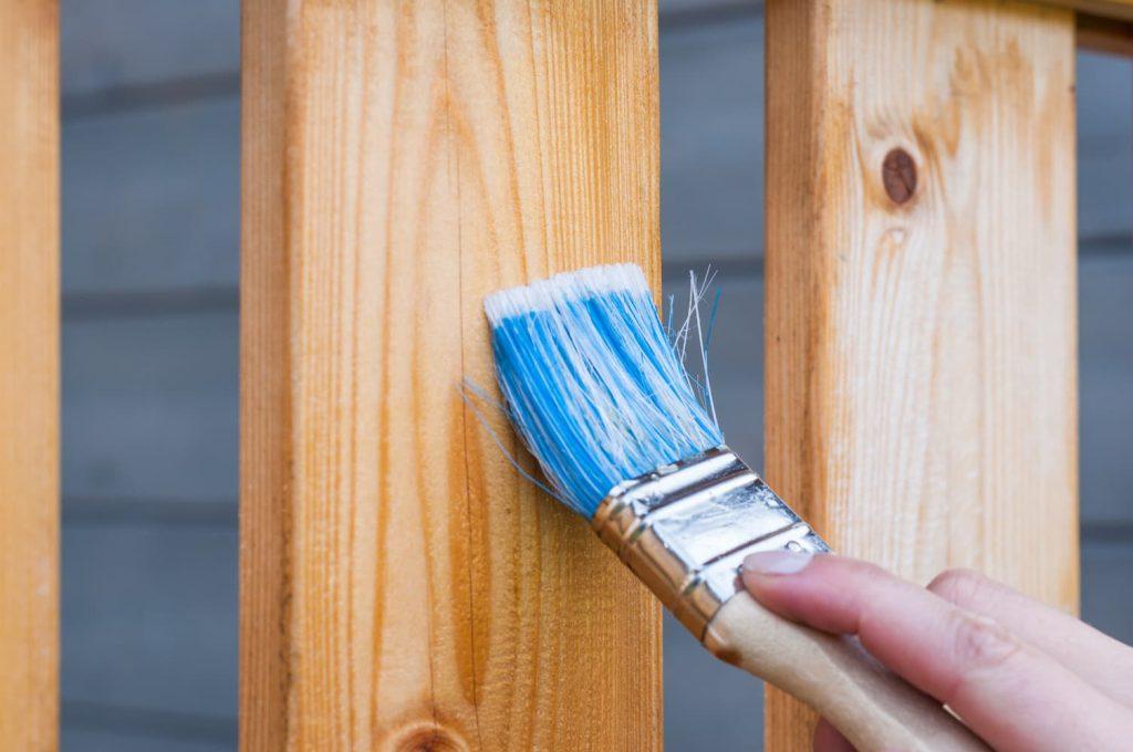 Pessoa pintando madeira com um pincel simples.