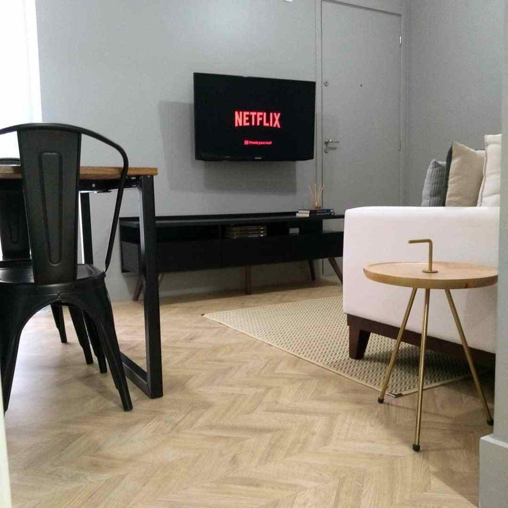 Sala de cliente pintada na cor cinza com um Rack Madesa preto e sofá branco.