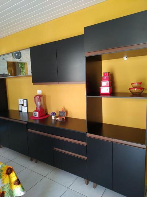 Cozinha Reims preta de cliente Madesa em frente a uma parede amarela.