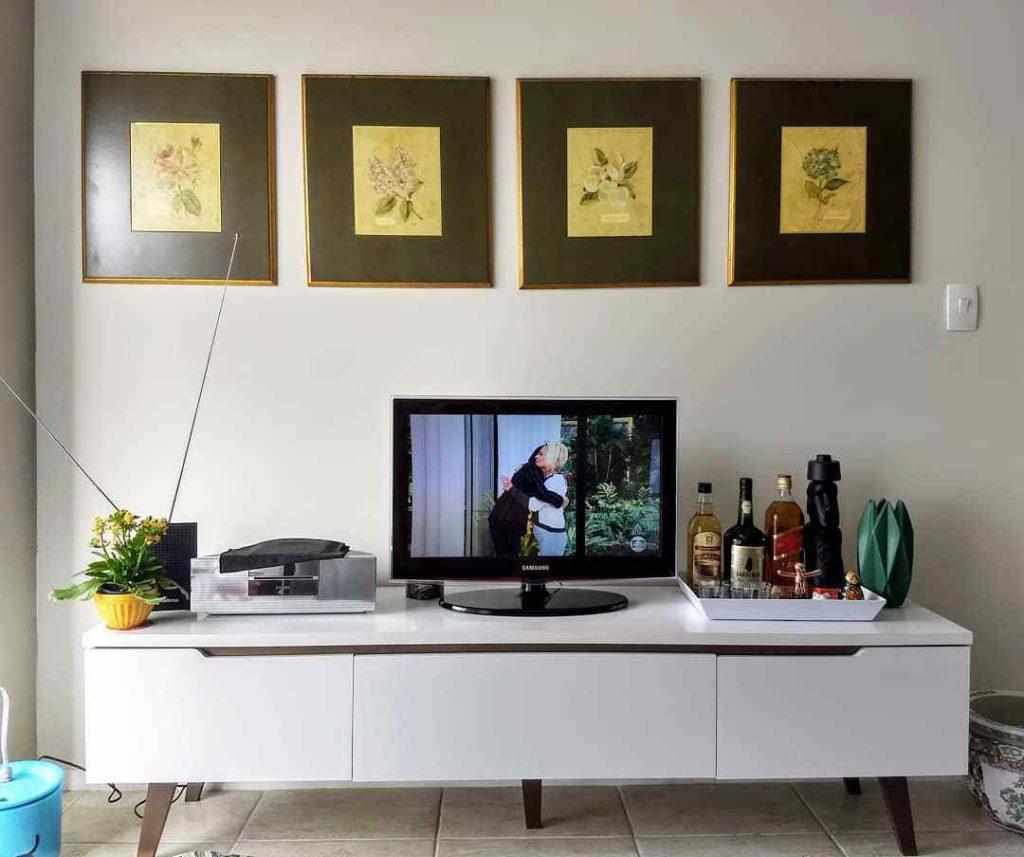 Sala de cliente Madesa decorada com rack Reims branco e quadros na parede.