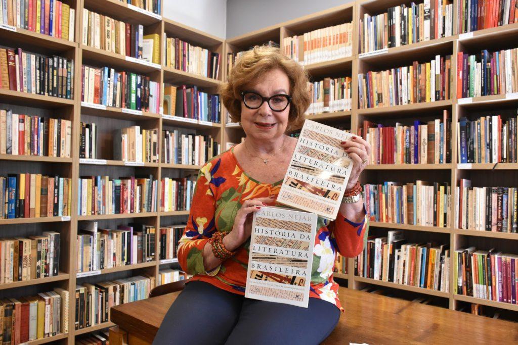 Mulher segurando alguns livros na biblioteca Jardim das Letras
