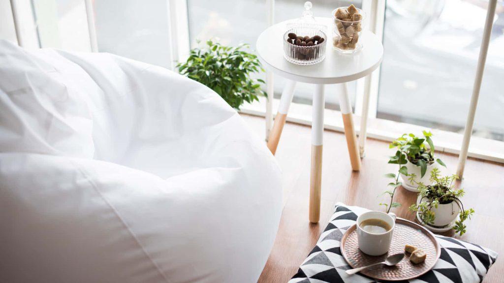 Cantinho decorado com vasos de plantas e velas, elementos comuns da decoração escandinava.