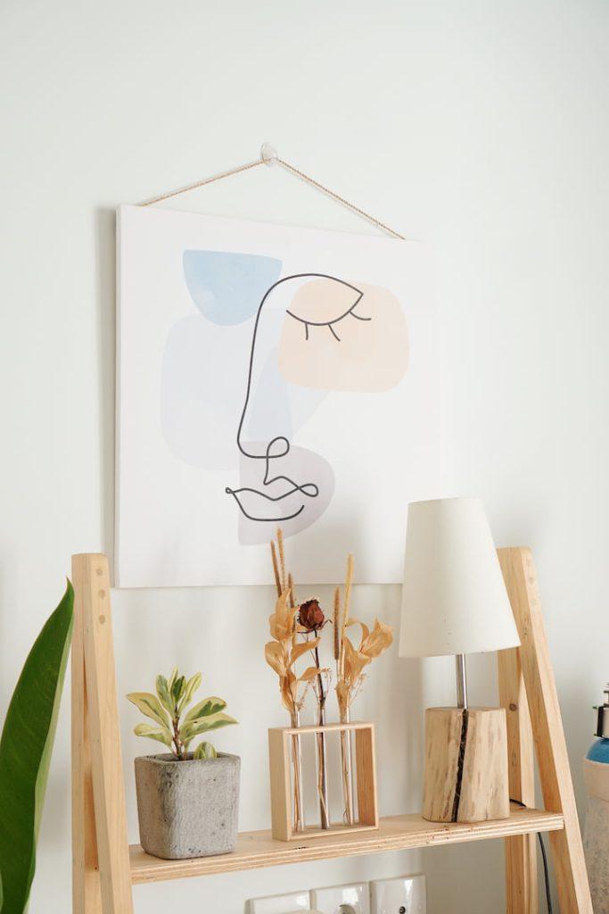 Estante de pinus decorada com vaso de concreto, abajur de madeira e um quadro minimalista, exemplos de o que é DIY.