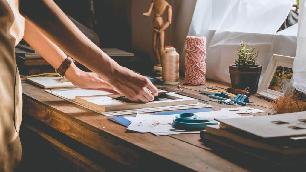 Pessoa criando um projeto de decoração DIY com quadros, fitas, linhas e outros materiais.
