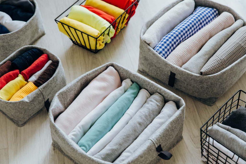 Roupas dobradas dentro de organizadores, uma ótima ideia de como organizar guarda-roupa.