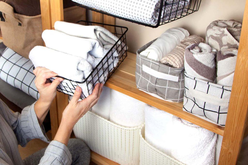 Toalhas acomodadas em caixas organizadoras, uma das melhores dicas de como organizar guarda-roupa.
